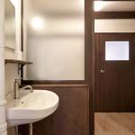 洗面器+鏡+棚のシンプルな洗面室。壁をつけて脱衣スペースを確保。